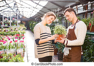 Cheerful woman with help of gardener choosing flowers in pot