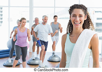 Cheerful woman with people exercising at fitness studio
