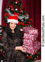 Cheerful woman with santa hat holding gifts