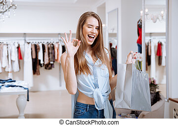 Cheerful woman with shopping bag showing ok in clothing store