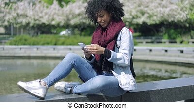 Cheerful woman with smartphone outside