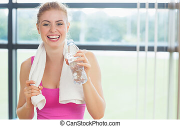 Cheerful woman with towel around neck holding water bottle
