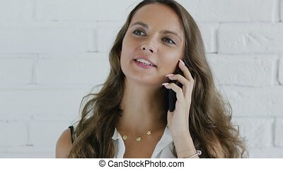 Cheerful woman with wavy hair speaking on smartphone