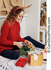 Cheerful woman wrapping Christmas gifts
