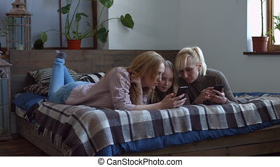 Cheerful women browsing the net on smart phones - Joyful...