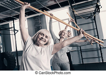 Cheerful women doing stretching with wooden exercise sticks