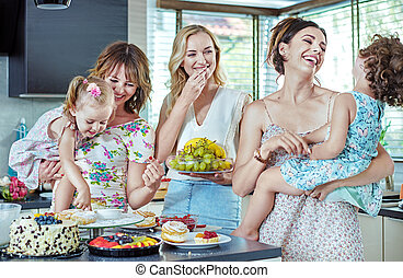 Cheerful women eating cakes and sweets with their children