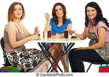 Cheerful women eating dessert at table