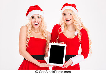 Cheerful women in santa cloth showing tablet computer screen