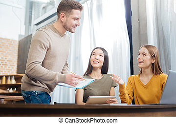 Cheerful women smiling while looking at the handsome young man