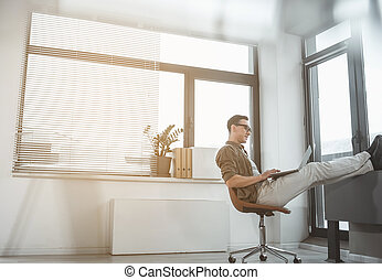 Cheerful worker typing in laptop