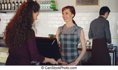 Cheerful workers of coffeehouse are greeting customers,...
