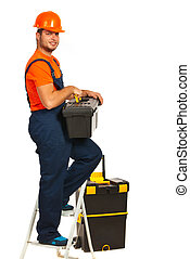 Cheerful workman standing on step ladder and holding box isolated on white background