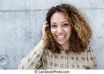 Cheerful you woman laughing with hand in hair
