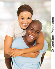 young african american couple having fun with piggyback