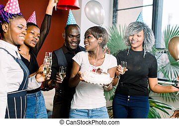cheerful young African company celebrates birthday and have a cake with candles