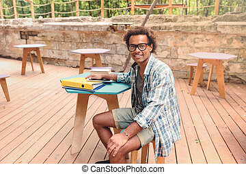 Cheerful young african man sitting in outdoor cafe