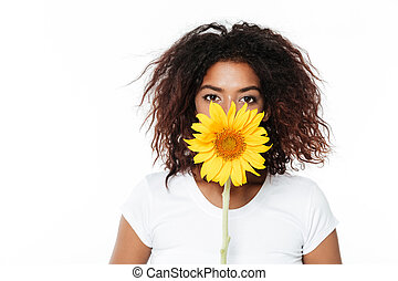 Cheerful young african woman holding flower.