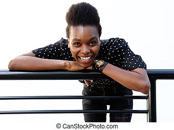 Cheerful young african woman leaning on railing