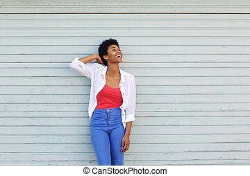 Cheerful young african woman looking up at copy space