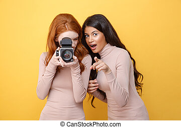 Cheerful young african woman pointing while redhead lady photographing