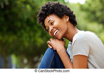 Cheerful young african woman sitting outdoors