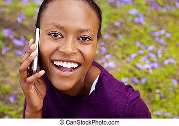 Cheerful young african woman talking on cell phone