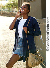 Cheerful young african woman talking on mobile phone