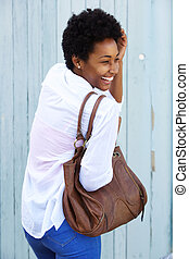 Cheerful young african woman with a purse