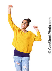Cheerful young african woman with arms raised