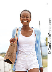 Cheerful young african woman with bag