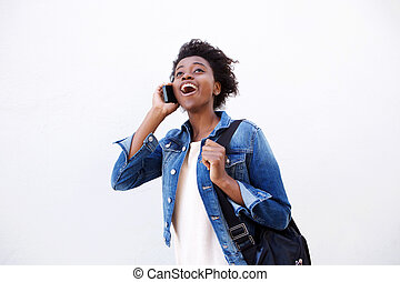 Cheerful young african woman with bag talking on mobile phone