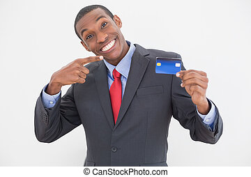 Cheerful young Afro businessman pointing at credit card