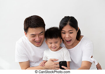 Cheerful young Asian family with son making selfie and smiling with mobile phone on front camera isolated on white background