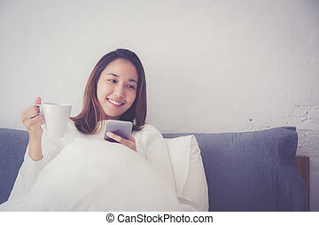 Cheerful young asian woman sitting in bed with smartphone and drinking coffee at home in bedroom.