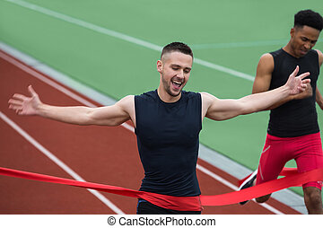 Cheerful young athlete man crossing finish line