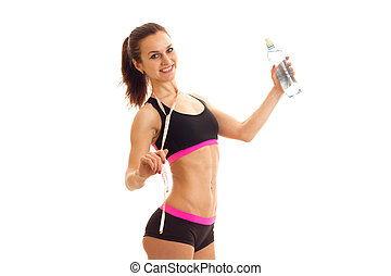 cheerful young athletic girl in tank top and shorts looking at the camera and holding a water bottle
