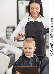 Cheerful young barber is using dryer in hairdressing salon