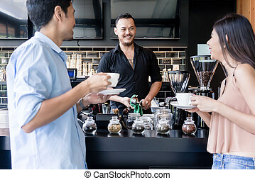 Cheerful young bartender cleaning the coffee maker while talking