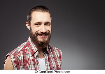 Cheerful young bearded guy is expressing positive emotions