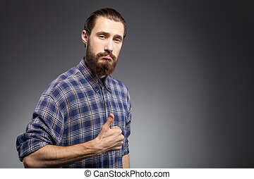 Cheerful young bearded guy is gesturing positively