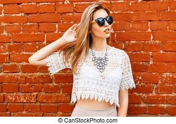 Cheerful young beautiful woman in sunglasses posing near brick wall