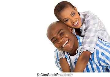 young black couple piggybacking