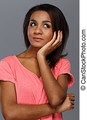 Cheerful young black woman isolated on grey background