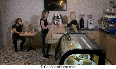 Cheerful young blonde barista worker serving coffee to go to a female client in a cafe
