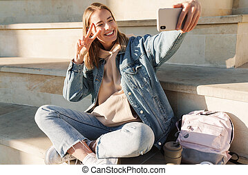 Cheerful young blonde girl taking a selfie with mobile phone while sitting on steps otdoors, peace gesture