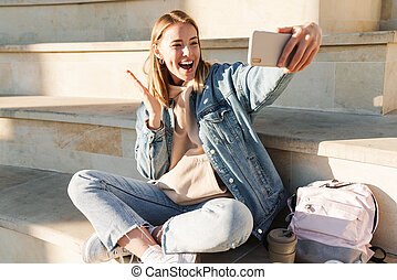 Cheerful young blonde girl taking a selfie with mobile phone while sitting on steps otdoors
