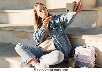 Cheerful young blonde girl taking a selfie with mobile phone while sitting on steps otdoors, sending kiss