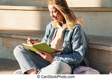 Cheerful young blonde girl taking notes while sitting on steps otdoors