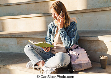 Cheerful young blonde girl taking notes while sitting on steps otdoors, talking on mobile phone
